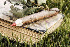 Wooden pencil and old book Royalty Free Stock Photos