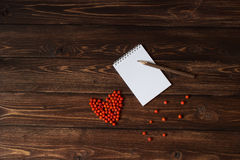 Wooden pencil on the open notebook and red ashberry as a heart shape at the table Stock Photos