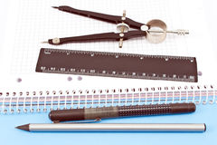 Wooden pencil, pen, drawing compass and ruler on spiral notebook Royalty Free Stock Photo