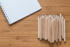 Wooden pencils on desk. Pile of sharpened wooden pencils next to open notebook on wood desk Royalty Free Stock Photography