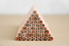 Wooden pencils stacked in a pyramid shape. Wooden pencils with gray slate stacked in a pyramid shape on a brown surface in perspective Stock Photography