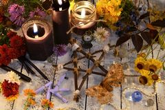 Wooden pentagram with moth - death symbol, black candles and flowers on planks. Occult, esoteric, divination and wicca concept. Halloween vintage background stock image