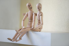 Wooden people sitting at home in quarrel Stock Photos