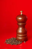 Wooden pepper mill with black peppercorn. On the red background Stock Image