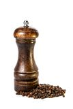 A wooden peppermill with peppercorns on white background Stock Photography