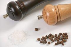 Wooden peppermills. Salt and peppercorns closeup stock photos