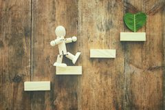 Wooden person and a heart shaped leaf. ecology and recycling concept. Wooden person and a heart shaped leaf. ecology and recycling concept Royalty Free Stock Images