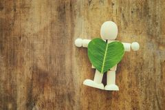 Wooden person holding a heart shaped leaf. ecology and recycling concept. Wooden person holding a heart shaped leaf. ecology and recycling concept Royalty Free Stock Images