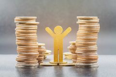 Wooden person model and coins stacks stock images