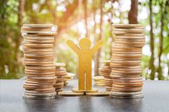 Wooden person model and coins stacks, royalty free stock image