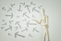 Wooden person standing with his back in front of textured background full of arrows pointing in different directions Stock Photo