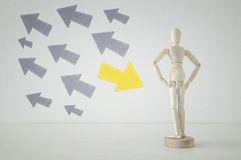 Wooden person standing with his back in front of textured background full of arrows pointing in different directions Stock Image