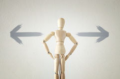 Wooden person standing with his back in front of textured background full of arrows pointing in different directions Stock Photos