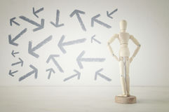 Wooden person standing with his back in front of textured background full of arrows pointing in different directions Stock Photography