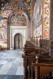 Colorful fresco lined corridor with wooden pews, Rila Monastery, Bulgaria stock image