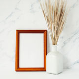 Wooden photo frame mockup, bouquet of barley spikelets. In front of pale marble pastel background Royalty Free Stock Photos