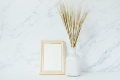 Wooden photo frame mockup, bouquet of barley spikelets Stock Image