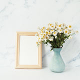 Wooden photo frame mockup, bouquet of white chamomile. In front of pale marble pastel background Stock Image