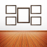 Wooden photo frames on white wall inside the room Royalty Free Stock Photography