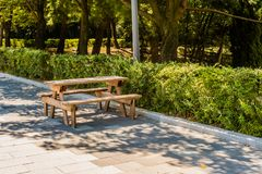 Wooden picnic table in park next to hedges. Wooden picnic table on concrete block sidewalk in park next to wooded area lined with hedges Royalty Free Stock Photography