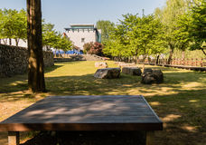 Wooden picnic table in a public park shaded by trees with a wood Stock Photography