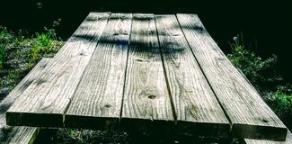 Wooden picnic table  in shaded grass. Rugged wooden picnic table in shaded grass Royalty Free Stock Images