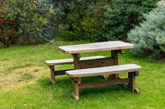 Wooden picnic table and two benches outdoors royalty free stock image
