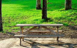 Wooden picnic table on wooded green scenery Stock Image