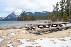 Wooden picnic tables on mountain lake Stock Photo