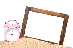 Wooden picture frame and alarm clock. On the beach Royalty Free Stock Photo