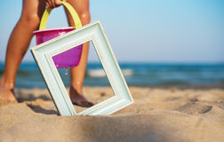 Wooden picture frame on the beach sand, summer concept. Children play in the sand beach Stock Images