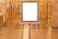 Wooden picture frame on easel in art gallery Stock Photos