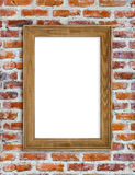 Wooden picture frame hanging on red brick wall