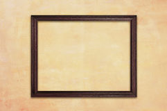 Wooden picture frame on retro yellow concrete wall Stock Photo