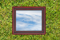 Wooden picture frame with view of sky, on green grass wall backg Stock Photos