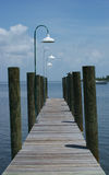 Wooden pier. Wooden peir with white overhead lights Royalty Free Stock Images