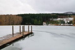 Wooden pier. In winter with frozen water royalty free stock photo