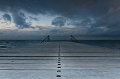 Wooden pier. A wooden pier with two ladders by the ocean Royalty Free Stock Image