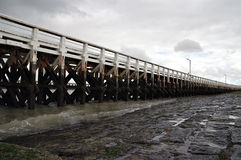Wooden pier. Exterior of wooden sea pier receding into distance with slipway in foreground Stock Image