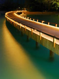Wooden pier. With night illumination and reflection in the sea Royalty Free Stock Image
