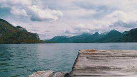 Wooden pier on the background of a mountain lake and snowy alps. Austria. Wolfgangsee lake. Beautiful landscape for relaxation. Idyllic, solitude with nature stock video footage