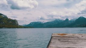 Wooden pier on the background of a mountain lake and snowy alps. Austria. Wolfgangsee Lake. Beautiful landscape for relaxation. Idyllic, solitude with nature stock footage