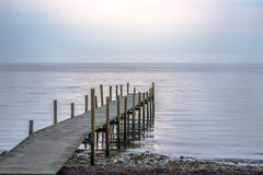 Wooden pier at beach on a calm morning Stock Photos