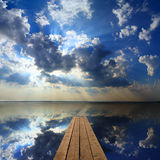 Wooden pier on big lake and sky reflection Stock Photo