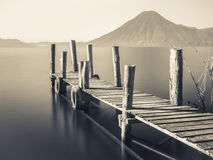 Wooden Pier Black and White. An old wooden pier juts out into lake Atitlan in Guatemala with volcano in background Royalty Free Stock Photography