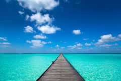 Wooden pier with blue sea and sky background Stock Image
