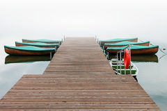 Wooden pier with boat. Look on autumn foggy lake with wooden pier with boat stock images