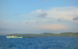 Wooden pier with a boat. A wooden pier with a boat, the island of Siargao in the Philippines Stock Photos