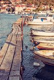 Wooden pier with boats in harbor, Trogir, Croatia, red filter Royalty Free Stock Photos