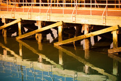 Wooden pier for boats and its reflection in the sea water. Toned Royalty Free Stock Photos